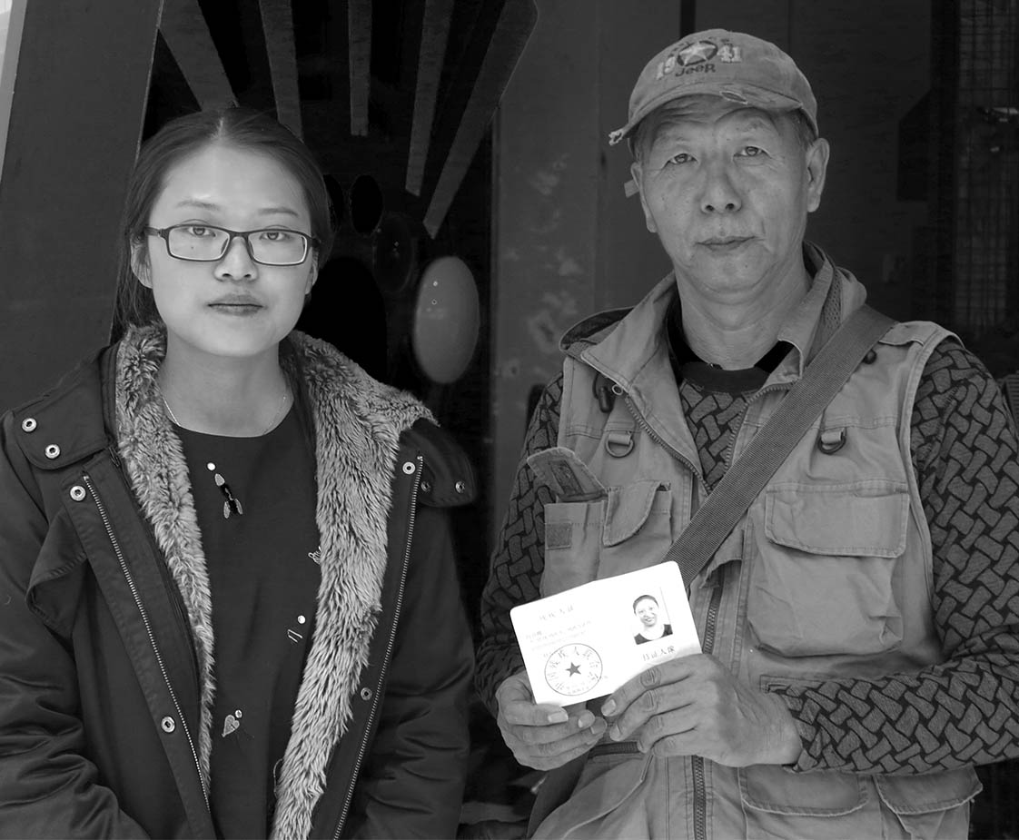 Reporter Wang Li Juan poses for a photo with Lu Gang as he holds his wife's ID resident card. (Jock Lauterer photo)