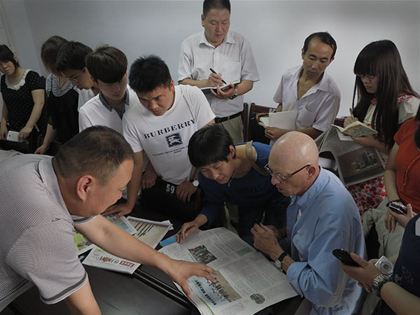 Publisher Yuan, left, and the staff of the fledgling Deng Feng Golden Edition pay attention as Mr. Joke gives a coaching session. (Photo by Li Tao)
