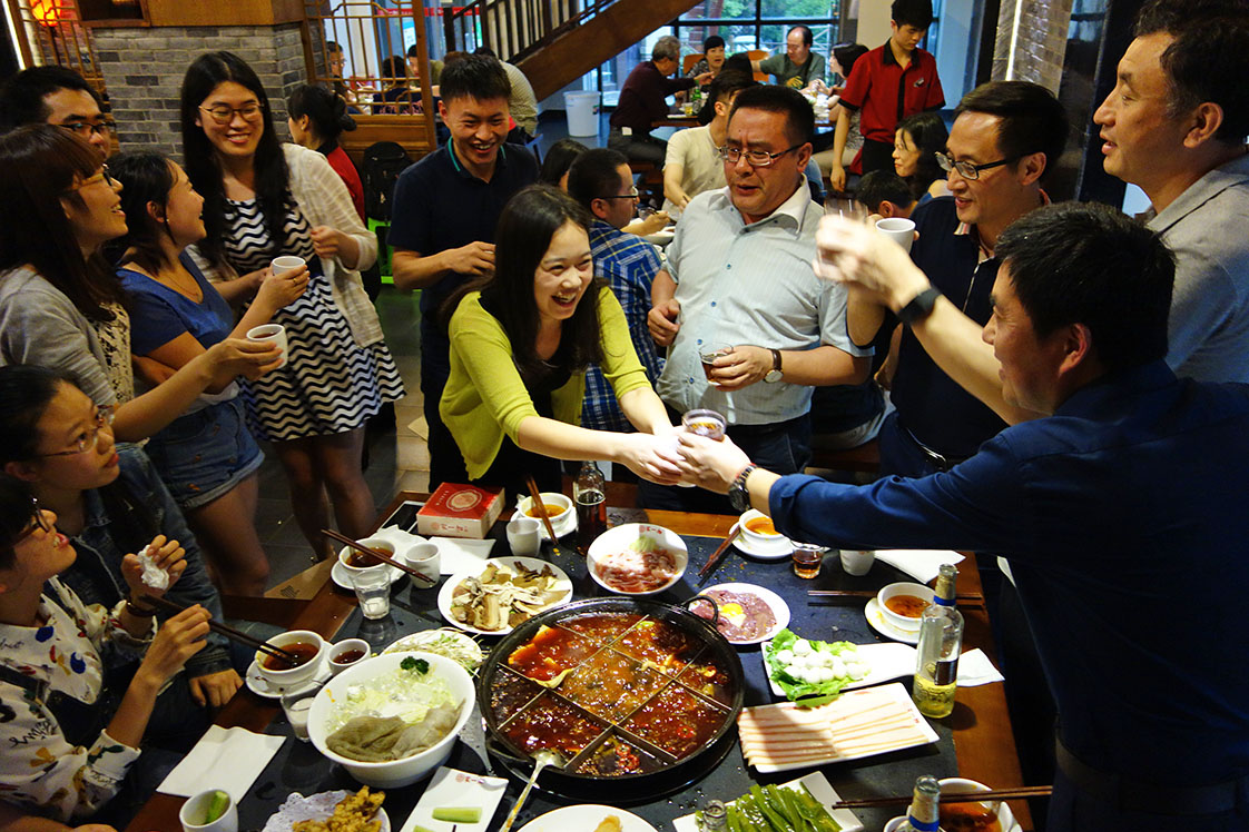 Following the successful conclusion of the seminar on community journalism, attendees at a local hotpot restaurant toast conference organizer Prof. Li Ren, center. (Jock Lauterer photo)