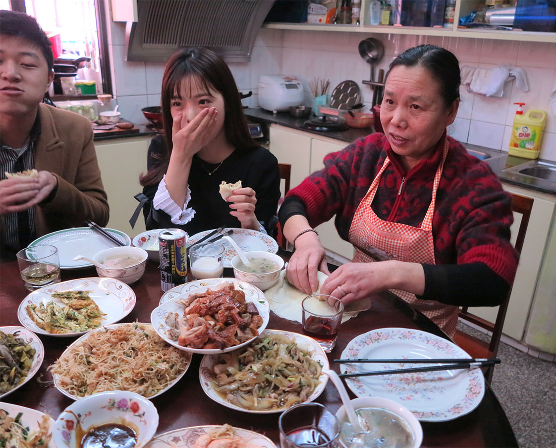 "Lunch at mama Ying's: they served homemade elderberry wine for lunch. Center is a reporter named ""Fanny,"" who, at 24, fears she will be a ""left-over woman."" At far left is another reporter for the paper. (Jock Lauterer photo)"