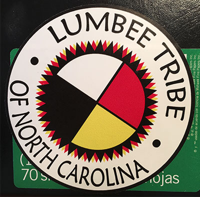 The Lumbee Tribe logo: the circle, the pinecone patchwork and the four colors — all with deep symbolic meaning.