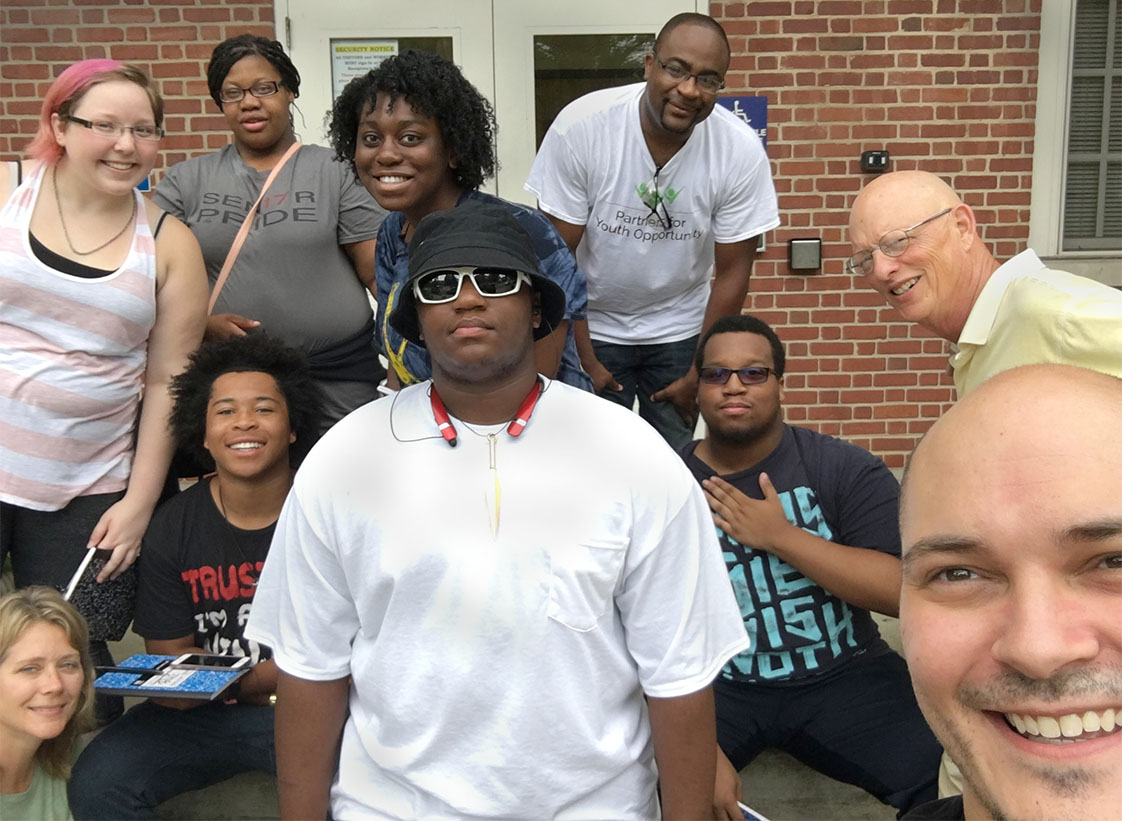 "UNC Prof Joe Cabosky shoots a ""selfie"" with the Durham VOICE Ocracoke team: from center clockewise, LaMon James, Julie Wells, Bruce Wilkinson, Christian Larence, Natasha Graham, Carlton Koonce, Yusuf Shah and Jock Lauterer."