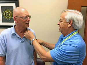 """Newly inducted honorary Lumbee Tribe member, Jock """"Locklear,"""" gets his pin from tribal administrator Dock Locklear. (James Locklear photo)"""