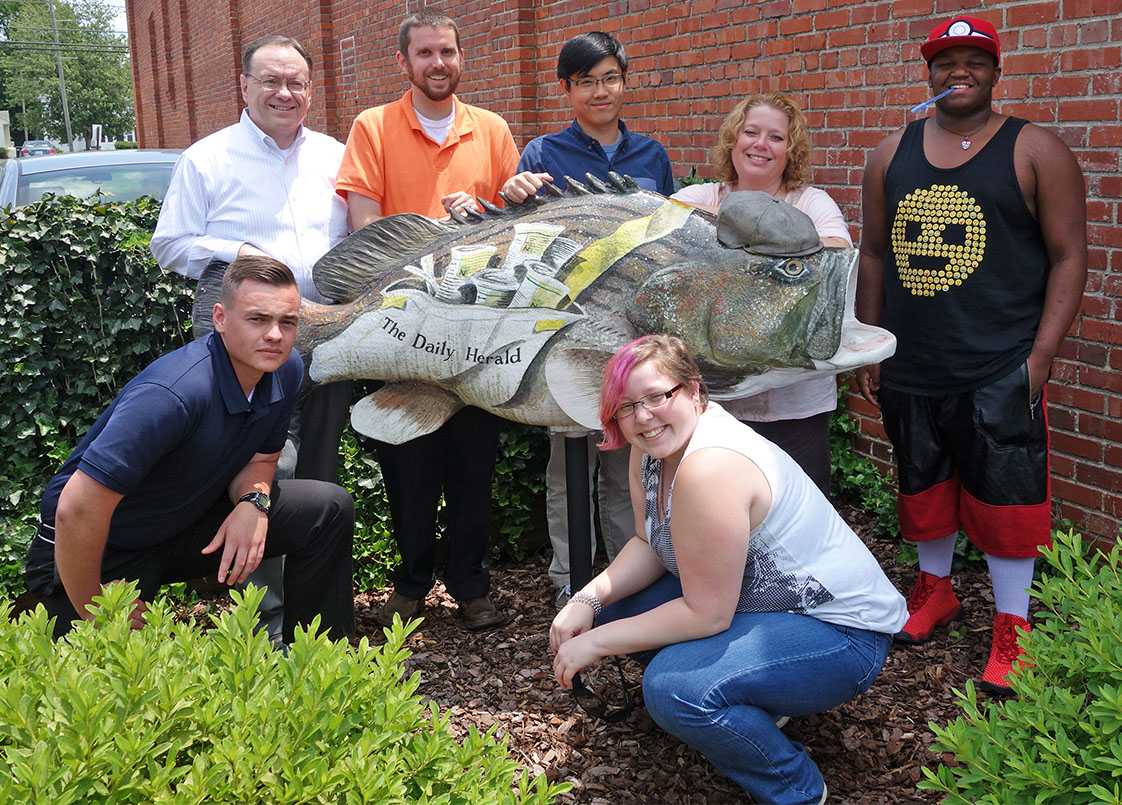 Gathered around a large-mouth bass piece of public art outside the Daily Herald, the staff gathers with Durham VOICE staffers. (Jock Lauterer photo)