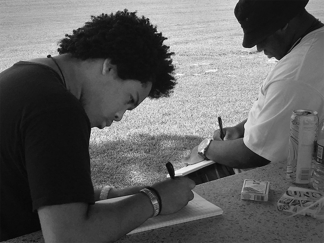 Part of the purpose of the trip is to develop writing skills. The Durham VOICE team, sponsored by Partners for Youth Opportunity, keeps a daily journal to record the sights, sounds, feels and impressions of Ocracoke Island. Young writers, left to right, Bruce Wilkinson and LaMon James take pen in hand to put thoughts on paper. (Jock Lauterer photo)