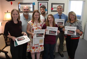 Garner Citizen staffers proudly hold up fresh copies of their paper, hot off the presses. The paper's owners are Barry Moore, second from left, and Debbie Moore Rodwell, far right. ( Photo by Jock Lauterer)